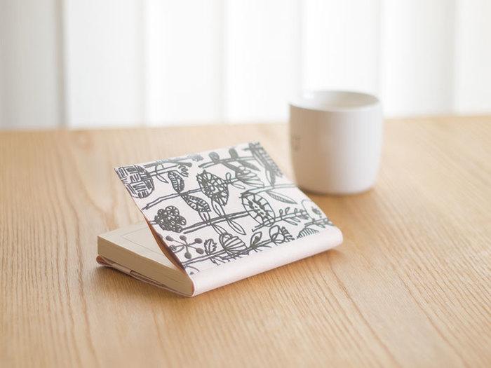 植物の文様が素敵なブックカバーはSIWAとのコラボレーションです。和紙ならではの質感がミナペルホネンのデザインと良く似合います。
