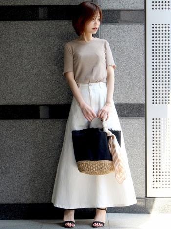 カジュアルだけど女性らしい白のデニムロングスカート。シンプルなベージュカットソーやほぼ黒で統一されたバッグとサンダルを合わせてシンプルに。