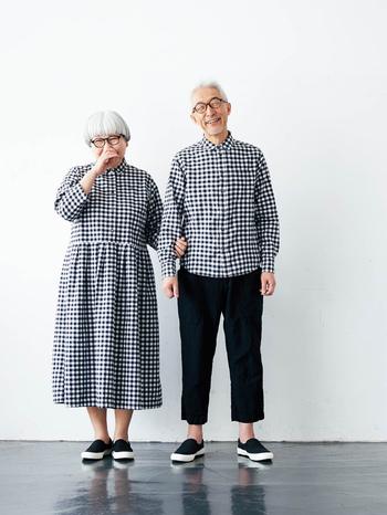 """もともと『サニークラウズ』をインタビューなどで""""好きなブランド""""に挙げていたbonponご夫妻。今回、縁があってコラボすることになったそうです。 一つ目のリンクコーデは黒×白のギンガムチェック。bonさんはベーシックなシャツ、ponさんはウエストにタックの入ったワンピースです。ワンピースは以前に、「着用した写真をインスタにアップしたところ好評だった」というエピソードから、そのワンピースをベースにしたデザインに。「夏でも長袖」「首元は詰まり気味が好き」など、二人のこだわりがちゃんと取り入れられています。"""