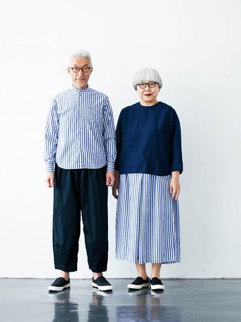 """二つ目のリンクコーデは、夏らしいブルーのストライプがモチーフです。bonさんは「普段あまり着ない」スタンドカラーシャツに挑戦。ponさんのボトムスはスカート見えするキュロスカートで楽ちんです。ネイビーのトップスもコラボアイテムで、コーディネートがばっちり決まります。扱いやすい綿100%の生地は、お二人が厚みや肌ざわりを実際に確認して選んだものだそう。 トレードマークである""""めがね""""の刺しゅうや、""""bonponオリジナルネームタグ""""もいい感じです。"""