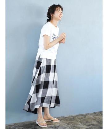夏の装いのアクセントには、おしゃれなチェック柄スカートもおすすめです。存在感抜群のビッグギンガムチェックなら、定番のTシャツコーデも新鮮な印象に。裾に向かって広がる上品なフレアラインと、シックなモノトーンの配色が大人っぽい雰囲気で素敵ですね。