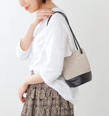 バケツ型の小ぶりなカゴバッグは、レザーとカゴを組み合わせた大人っぽいデザインが特徴。長すぎないストラップで、さっと肩から掛けるスタイリングが上品にきまります。