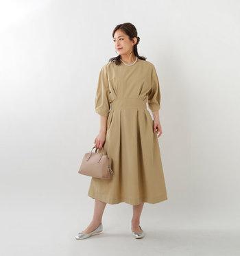 ウエストと袖がキュッと締まったパフスリーブで、女性らしいメリハリのあるシルエットのベージュワンピース。一枚でベーシックに着こなすのはもちろん、ちょっとしたお呼ばれスタイルにも活躍してくれるアイテムです。