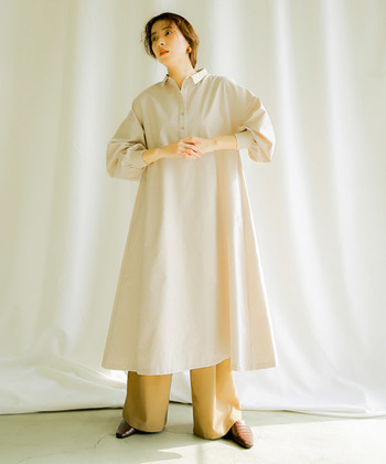 ロング丈のシャツワンピースは、ちょこんと付いたミニサイズの襟が特徴の一枚。ゆったりAラインのシルエットと、キュッと締まったパフスリーブがナチュラルな中にトレンドを感じさせるデザインになっています。