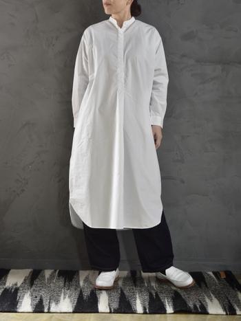 シンプルな白のロング丈シャツワンピースに、ダークトーンのワイドパンツを合わせた着こなしです。足元は白のローファーシューズで、ベーシックながらも大人の余裕を感じさせるスッキリコーデに。