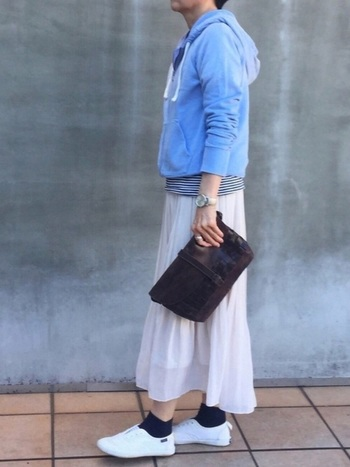 きれいな水色のギャップのパーカには、白のギャザースカートを合わせてキレイ目カジュアルに。