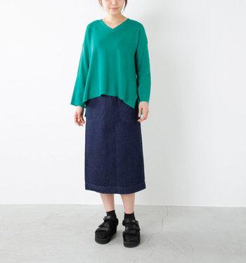 長めの着丈と程よいタイト感で、年齢を選ばずに着用できるベーシックなデニムスカート。グリーンのキレイ色トップスを、あえてタックインしない着こなしで大人っぽさをしっかりアピールしています。