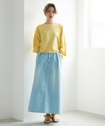 爽やかな印象を与えるサックスカラーのデニムスカートは、春夏の季節にぴったりなアイテム。イエローのトップスを合わせて、着るだけで元気いっぱい気分になれそうなカラーリングでまとめています。