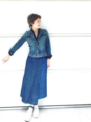 デニムのデザイン切替ロングスカートに、デニムジャケットを合わせたコーディネートです。インナーには、上品な印象を与えるネイビーのシャツをオン。デニムオンデニムコーデが気になる40代~50代の女性にも、ぜひ挑戦してほしいスタイリングです。