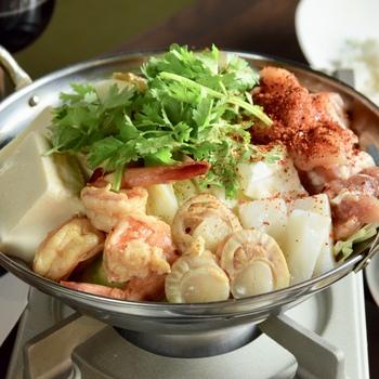 こちらは、パクチー盛り盛りなトムヤム鍋。 トムヤムとパクチーは間違いない組み合わせですね♪  シーフードの旨味とパクチーの風味がたまらない鍋です。