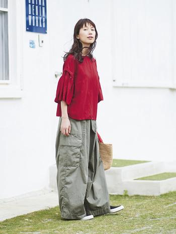 """フリルになった袖と真っ赤なカラーが、どことなく金魚をイメージさせるトップスは、とろみと落ち感のある生地を使って袖のボリュームを抑えて着やすく。ユニークなデザインが目を引く、コーデの主役になるアイテムです。 ワイドシルエットのカーゴパンツは張り感があり、デイリーに穿くのにちょうどいい感じ。フロントがタイパンツを思わせる独特なデザインで、さりげなく個性的な仕上がりです。カジュアルもきれいめも、合わせるトップスを選ばない""""実力派""""パンツといえそう。"""