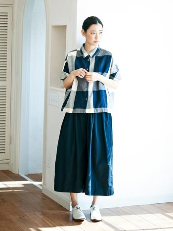 風合い豊かな綿麻の生地を使ったベーシックなデザインの半袖シャツは、ワイドなシルエットと短めの着丈が絶妙なグッドバランス。ボリュームのあるスカートやキュロットと相性抜群ですが、すっきりとしたパンツと合わせても着こなせます。 ラインナップは、大きなモノトーンチェック柄と黒無地の2色展開。