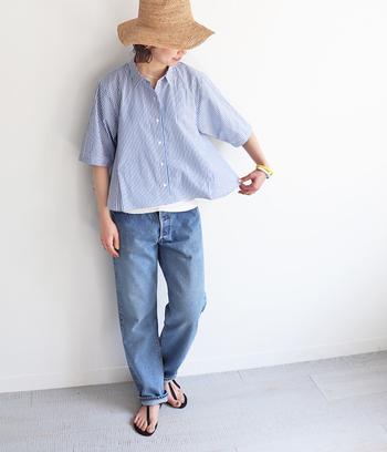 ショート丈のストライプシャツは、デニムとサンダルを合わせてカジュアルダウン。ナチュラルなハットをかぶって、上品見えシャツを休日スタイルに落とし込んだ着こなしです。