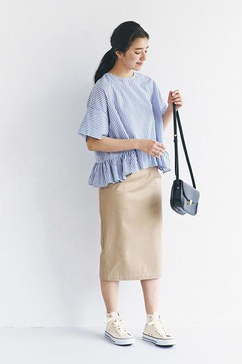 ぺプラムデザインが着映えする、青と白のストライプトップス。ベージュのタイトスカートにスニーカーを合わせた、カジュアルフェミニンな着こなしです。黒のショルダーバッグで、大人感をプラスしているのがポイント♪