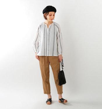 ストライプの刺繍が入った白のブラウスを、ブラウンのテーパードパンツに合わせたコーディネートです。きちんと感のあるアイテム同士に、黒のサンダルとベレー帽でラフ感を演出しています。