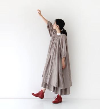 ちょっぴり透け感のあるカーキベージュのワンピースに、同じカラーのスカートをレイヤード。技ありなのにナチュラルに見える、上級者風コーデに仕上がります。赤の靴を合わせて、差し色をプラス。