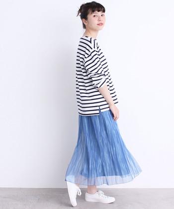 サックスブルーのプリーツスカートに、ボーダーのトップスをあえてタックインしないコーディネートです。足元は白スニーカーで爽やかに。スカートの透け感が、夏らしさを感じさせる着こなしですね♪