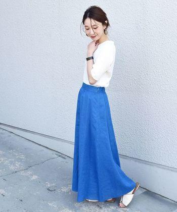 リネン素材で軽やかに揺れる、ロイヤルブルーのフレアスカート。白のトップスをタックインして、白サンダルを合わせた爽やかカラーで着こなしています。カーディガンを肩から羽織っても、女性らしいスタイリングに。