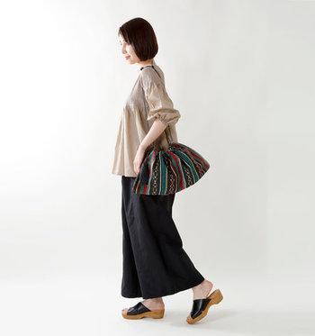 数種類のカラーを組み合わせた色合いが、カジュアルにもフェミニンスタイルにも合う巾着バッグ。ベージュのブラウスとクロのワイドパンツを合わせたナチュラルスタイルも、アクセントになるバッグがあればエスニックコーデに早変わりします。