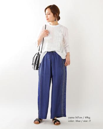 エスニックデザインのブルーのワイドパンツに、白のレースブラウスを合わせたコーディネートです。レース刺繍もエスニックな雰囲気のある柄で、夏らしい爽やかなスタイリングがとってもおしゃれ♪