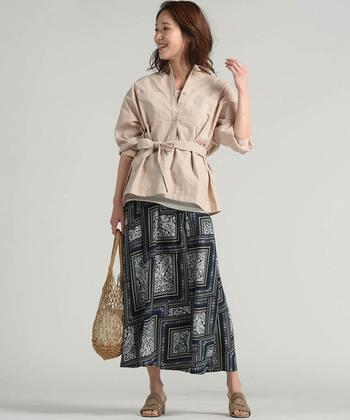 モノトーンのスカーフ柄スカートで、エスニックムード漂う着こなしに。ベージュのデザインシャツを合わせて、個性派になり過ぎない上品コーデにアップグレードしています。