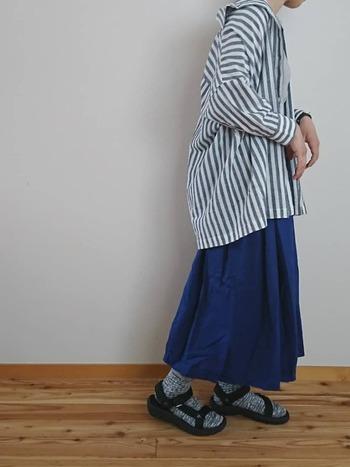 ビッグシルエットのシャツは、襟を抜いてゆるっと着こなしましょう。濃いブルーのスカートをあわせて、コーデを引き締めて。スカートの濃いブルーを活かすように、靴下は優しい色味をあわせてあげましょう。