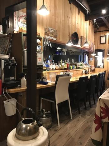 木の温もりいっぱいの店内は、テーブル席の他、カウンターもあります。キッチン奥には大きなピザ釜が。