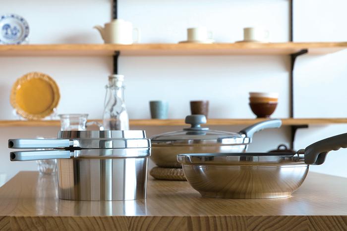 """無水鍋の良さを受け継ぎながらも、さらに日常使いに大活躍してくれる""""HALシリーズ""""の無水鍋。写真一番奥にあるのが万能無水鍋23cm、右前が26㎝です。中華鍋のような形が特徴で、厚手のアルミニウムで作られています。 メタリックコーティング加工と呼ばれるフッ素樹脂加工が施されているので、食材が焦げ付きにくくお手入れも楽ちんです。蓋をして蒸し焼きにすると、ふっくらとした仕上がりに…。  写真左にあるのが「浅鍋」「深鍋」「ガラス蓋」が便利な1セットになったもの。程よいサイズ感がお弁当作りや、日々のおかず作りにとても重宝します。 浅鍋は、煮魚を作ったり、ミニフライパンとしてパンケーキを焼いたりと、何かと登場の機会が多くなりそう…。 深鍋は、一見すると小ぶりに見えますが、実は見た目よりも大容量。炊飯なら約2.5合を炊くことができ、深さがあるので揚げもの調理にも最適です。 そして、調理中の様子が一目で分かるガラス蓋は浅鍋、深鍋、どちらの鍋にも使用可能。"""