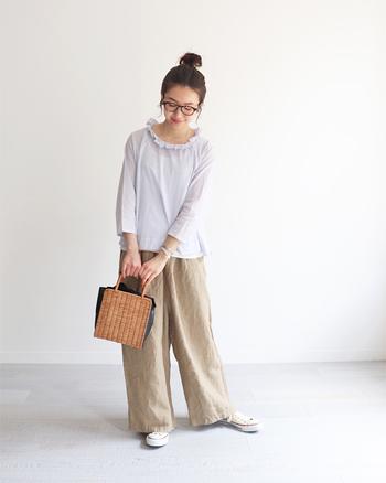 ワイドシルエットのリネンパンツにフェミニンなトップスを合わせたスタイリング。シンプルだけど、ほんのりと甘さのある着こなしに、かごバッグのアクセントが映えるコーデです。