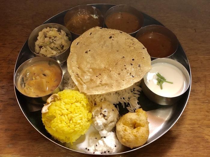 すでに、スパイスの魅力の虜になったフリークはさておいて、本格的なインド料理に馴染みのない方は、以下で紹介する定番人気のカレーや、インドの定食「ミールス」や、炊き込みご飯「ビリヤニ」から始めてみましょう。 【豆や野菜を使ったカレーや副菜など様々な料理がのせられた「エリックサウス八重洲店」の『ベジミールス』】