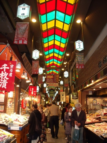京の台所として知られる「錦市場」。朱・緑・黄色の古代色が目を惹くアーケードが目印です。  地元の人から観光客まで、多くの人が訪れる活気溢れる商店街。