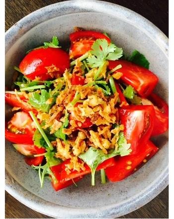 冷蔵庫から出したトマトをざく切りにしてボウルに。好みのハーブとともにすし酢・ごま油で加え、フライドオニオンを散らして。