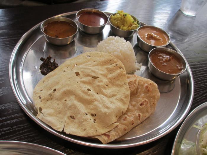 """「アーンドラ・キッチン」は、南インド料理をベースにしたレストラン。イチオシは、やはり""""ミールス""""です。 食材の持ち味を活かしたカレーや副菜は、素材の旨味やコクがしっかり。スパイス使いも実に巧みです。パリッとしたパパド、チャパティ、ライスも良く、タマリンドの酸味やスパイスの辛味が効いたラッサムも上品な味わいで秀逸と評判です。 【日替わりカリー3種の他、サンバル・ラッサム・ボリヤルなど、盛り沢山の""""平日の""""『ランチミールス』。】"""