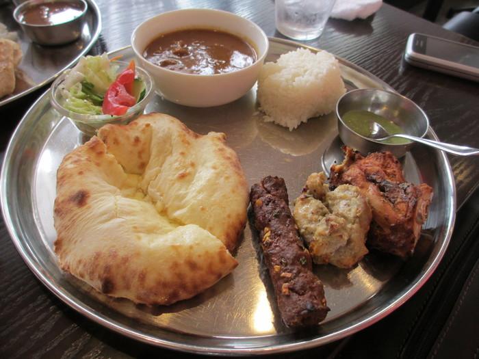 南インド料理がベースの店ですが、タンドール料理やナンもお勧めです。 中でも評判なのが、ナンの生地にチーズが入った『チーズ・クルチャ』。生地は、香ばしく焼き上げられてサクッとしながらも、噛むともっちりした食感。チーズのコクと塩気、ニンニクの風味が、小麦本来の甘味と旨味を引き立てて、パンチが効いて美味しい!と人気。  【日替わりカリー1種、タンドリーチキン、ガーリック・チキン、シークカバブ、チーズクルチャ(又はチャパティ、又はナン)、パスマティライス、サラダがセットになった、平日のランチメニュー『タンドゥーリ・セット』。】