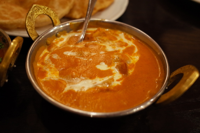 元々は英国生まれでインド国内に広がった「バターチキン」。 インドでは、カイエンペッパー等を加えて辛味を強くしていますが、バターや生クリームを使うため、味はマイルドで、日本人好み。老若問わず、誰もが食べやすいカレーです。  バターと生クリームの濃厚なコクと旨味、スパイスが一体となった味わいは、とろけるような美味しさ。辛味が苦手なら一押しのカレーです。【 マイルドで、旨みたっぷりと人気の「アーンドラ・ダイニング 銀座」の『バター・チキン』】