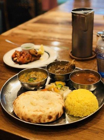 また、カレーやインド料理は、他のジャンルと比較して、着席してから提供されるまでの待機時間が短く、客の回転も良いため、人気店であっても無闇に待ち時間を取られる心配がありません。発車時刻を気にする方や時間に余裕がない方でも、満足する食事が頂けます。  【「グルガオン」のランチセット『グルガオンスペシャル』は、北インドならではのタンドール料理とカレー、店の名物チーズクルチャが楽しめる。】