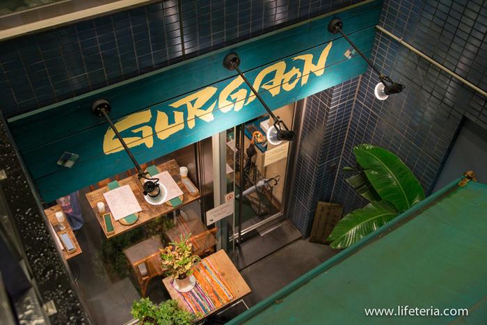 """「グルガオン」は、先に紹介したインド料理の名店「ダバ インディア」の姉妹店。銀座一丁目駅が最寄り駅ですが、東京駅からも徒歩圏。八重洲口から歩いて7分で到着出来ます。  「ダバ・インディア」は""""南インド料理""""がベースでしたが、「グルガオン」では、""""北インド料理""""をベースにした料理を堪能できます。【ビルの地下1階にある「グルガオン」の店入り口。インドの民家をイメージした店内は、明るく洒落た雰囲気。女性一人でも気軽に立ち寄れるカフェ風の店舗。】"""