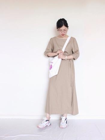 シンプルなベージュのロングワンピースに、ダッドスカートを合わせたコーディネート。バッグの斜め掛けや足元のボリューム感で、単調になりがちなワンピースコーデを今っぽくアップデートしています。