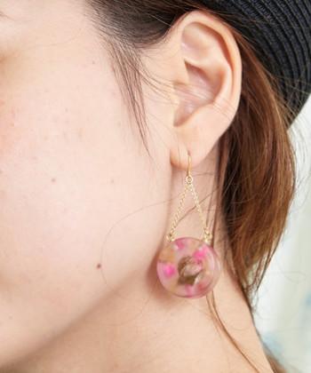 クリア素材の丸いピアスに、ピンク色のお花を閉じ込めた印象的なデザインです。揺れるチェーンが儚げな印象を与えるので、フェミニンなスタイリングに合わせて女性らしく仕上げるのがおすすめ♪