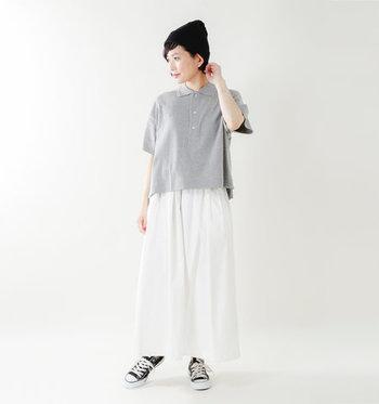 グレーのポロシャツに、白のフレアスカートを合わせたミックスコーディネート。黒のスニーカーとニット帽で、フェミニンな雰囲気を上手にカジュアルダウンしています。あえてタックインしないのが、大人っぽい抜け感を演出するポイント。