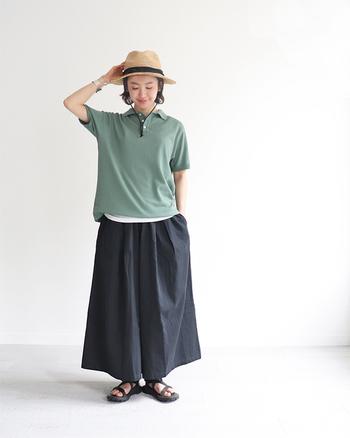 グリーンのポロシャツに、ネイビーのワイドパンツを合わせたコーディネート。あえてタックインせずに、白インナーの裾をちらりと覗かせたレイヤードスタイルがラフになり過ぎない着こなしのポイントです。