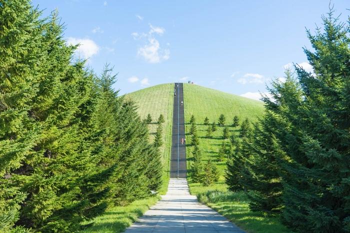 標高62.4mの「モエレ山」。モエレ沼公園のシンボル的存在となっている人工の山で、全部で登り口は3方向5ルート。このような一直線の階段のほか、山肌を回遊するルートもあります。色んなところを歩くたび、異なる山の表情や景色を楽しめます。