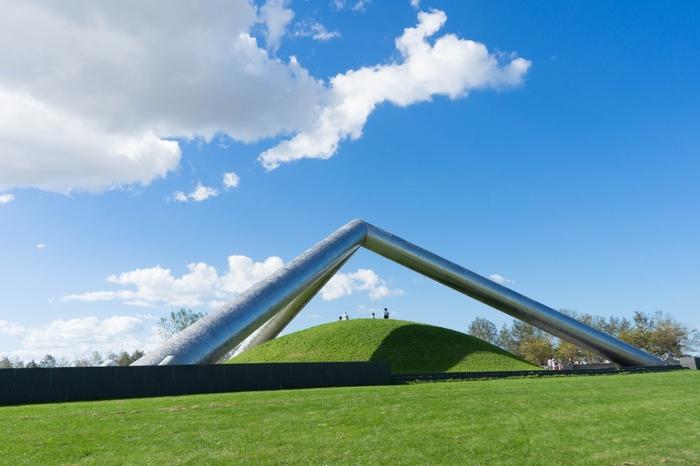 モエレ沼公園内には、美しい大型オブジェが多く点在しています。  こちらは直径2mのステンレスの円柱を組み込だ、三角のフォルムの作品「テトラマウンド」。本作品は公園の北側に位置しており、北西方向から園内を眺めると・・・白い一本道が続く「プレイマウンテン(標高30m)」、野外ステージ、「ガラスのピラミッド」など、三角形をモチーフとした主要なオブジェを一望できるようになっています。撮影スポットとしても、おすすめですよ。