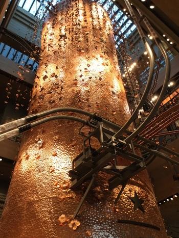 """吹抜けを貫いて4階まで伸びる銅製のキャスク。 豆の熟成と貯蔵庫の役割を果たすもので、高さ17メートルは世界5店舗の中でもトップとか。桜の木からインスパイアされただけに、周囲には銅製の桜の花びらたちがあしらわれています。 キャスクから縦横に伸びるパイプは豆を運搬するための""""シンフォニーパイプ""""。"""
