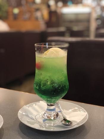 ベーシックな縦長のソーダグラスに入れられたメロンソーダのクリームソーダは、昭和モダンな雰囲気をあじわえる逸品です。缶詰の真っ赤なさくらんぼが添えられているのも定番です。