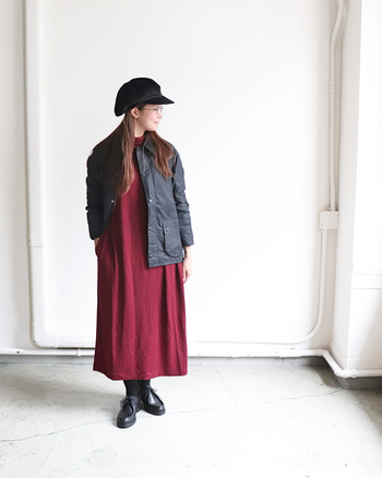 男っぽいデザインのバブアーに、女性らしい赤いワンピースを合わせてバランスのとれたコーデに。真逆のアイテムを組み合わせることでさりげなく個性を出すことができます。