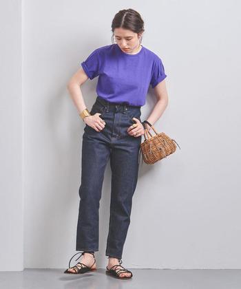 デニムとTシャツだって、色選びと小物使いでこんなに女性らしく。画像は、パープルのトップスとインディゴのデニムで落ち着いた色合いのコーディネート。華奢な編み上げサンダルと、小さなかごバッグでフェミニンさがプラスされた、大人のデニムスタイルです。