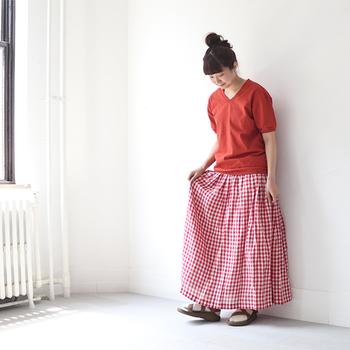 シンプルな赤のVネックTシャツに、ギンガムチェックの軽やかなスカートを組み合わせた、夏らしい素敵なコーディネート。白が入ることで、派手な印象になりませんね。