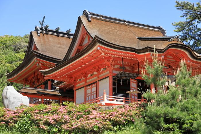 目にも鮮やかな朱に彩られた美しい神社。日本海と、折り重なるように茂る松林を臨む朱の社は、さながら竜宮城のようだと言われているそう。 神の宮に素戔嗚尊が、日没宮に天照大御神が祀られ、日本神話の中でも特に有名な二柱が鎮座する神社は、厄除けと縁結びのご利益があるとして古来より崇められてきました。