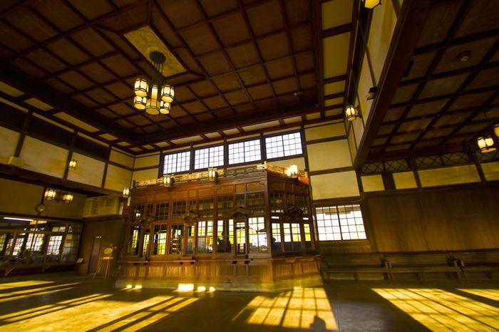 大正浪漫の雰囲気溢れる、ノスタルジックな駅舎の中。灯篭型の照明が30個も設置され、当時の人にとっては眩いばかりの空間だったに違いありません。 写真正面は二等待合室で、左奥が一般の待合室。昭和初期まで分けて使われていたそう。
